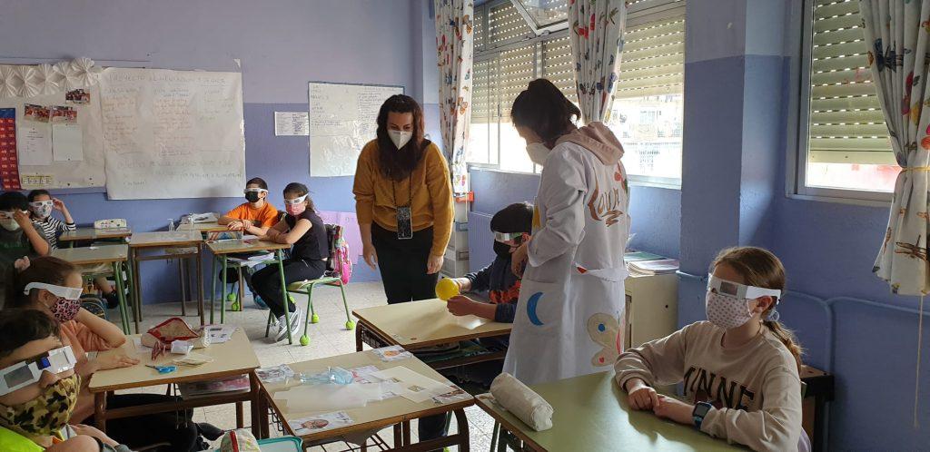 Trabajadora social Aroa y profesora junto a mesas con niños con gafas de baja visión